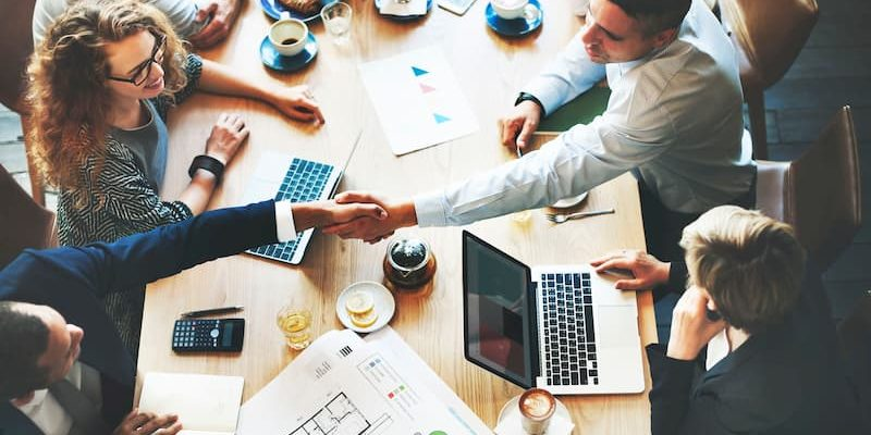 A handshake across the table in a boardroom meeting